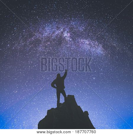 Champion man standing on a cliffs edge with raised hand against night landscape with milky way in a starry sky. Instagram stylisation.