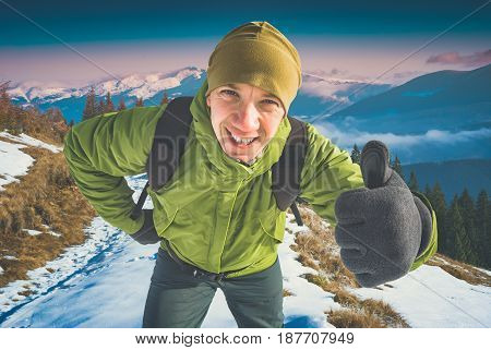 Cheerful active hiker with backpack showing thumbs up everything is OK and good. Majestic mountain valley covered with fresh snow. Instagram stylisation.