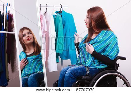 Real people disability and handicap concept. Teen girl handicapped woman sitting on wheelchair choosing clothes in wardrobe or looking for some clothes in shop