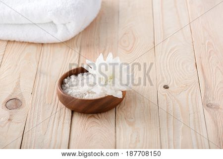 Close-up View Of Beautiful White Flower With Sea Salt And Towel On Wooden Table