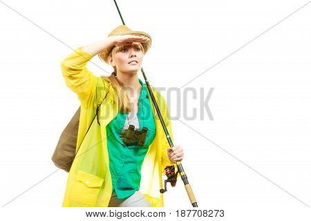 Fishery spinning equipment angling sport activity concept. Woman wearing raincoat holding fishing rod and binoculars ready for adventure.