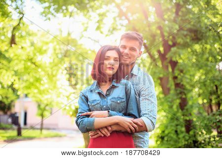 Happy funny couple standing outdoors and laughing on the bright sunny day and green summer background