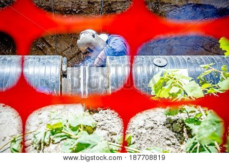 Welder is in trench arc welding pipeline. Confined space with orange plastic safety net