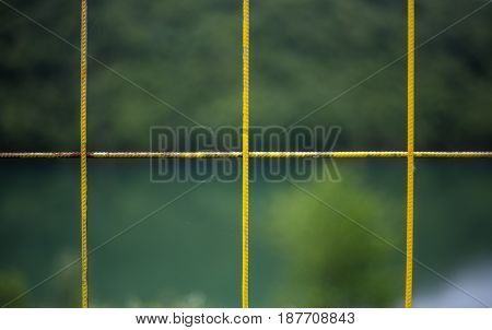Yellow improvised fence with a background of nature fence fittings