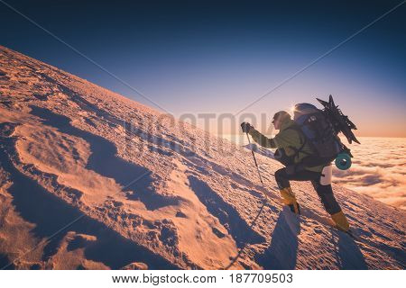 A climber with backpack climbs up a snowy mountain hill. Sunset sky on a horison. Instagram stylisation.