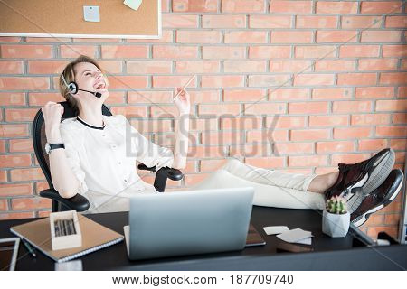 Cheerful employee wearing headphones with microphone is putting legs on table. She holding legs on table and laughing freely