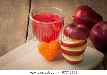 stack layer of slice red apple on wood cutting board and apple juice on glass.