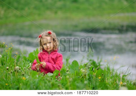 The little girl is on the green grass by the water. The child looks seriously at the lens. Concentrated look, curly hair, fleece jacket.. Children Protection Day.