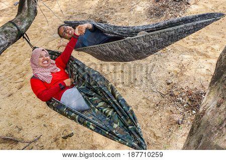 Labuan,Malaysia-Feb 19,2017:Young people relaxing & enjoying the hammock on tropical beach in Papan island,Labuan,Malaysia.