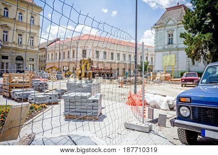 Wooden pallets with paving slabs are placed at building site in the city street.