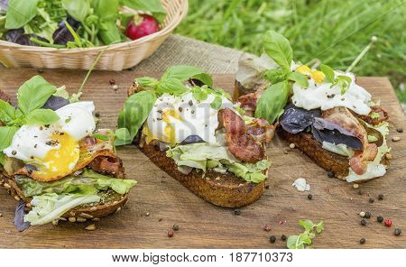 Poached eggs, lettuce and bacon on toasted bread. Natural healthy food concept.