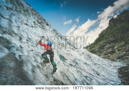Climber with axe in his hand climbs on a glacier to the top of the mountain. Caucasus Georgia Svaneti region. Instagram stylisation.