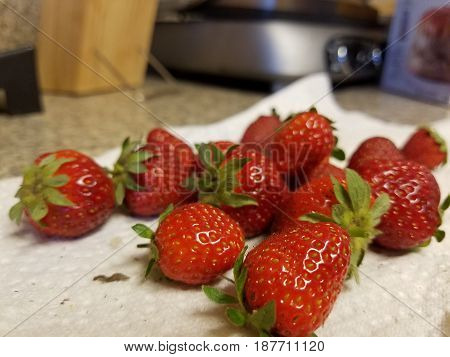 juicy red strawberries on paper towel on counter