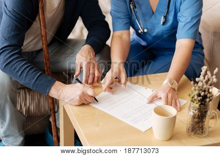Sign in here. Clever injured elderly man hiring a professional nurse for providing him medical services as he feeling unable leaving the house