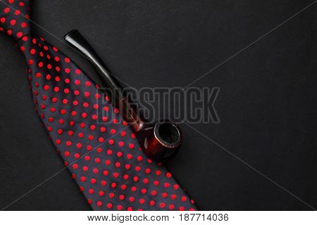 Classic Tie With Wooden Tobacco Pipe On Black Background With Space For Text, Top View. Greeting Car