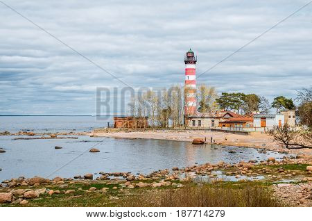 View of the cape on the coast with the old lighthouse in red and white stripes