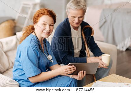 Exemplifying the lecture. Trained wise positive lady telling her patient everything about the process of treatment and employing tablet for illustrating her words