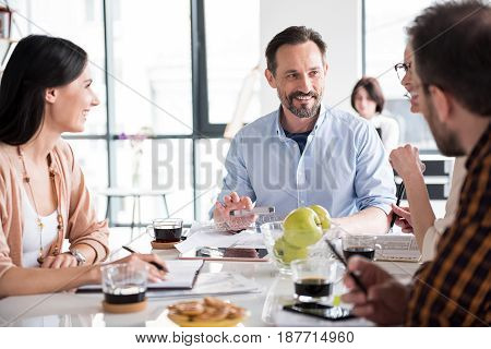 Happy employees are sitting around table and working on project. They holding pencils. People looking at each other with smile