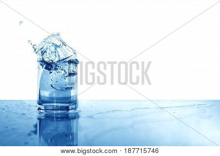Glass of splashing water with ice on white background with free space