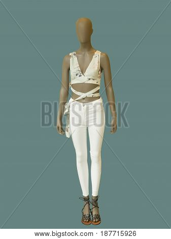 Full-length female mannequin dressed in white jeans and top isolated on white background. No brand names or copyright objects.