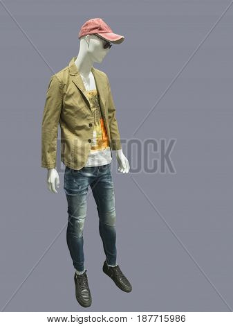 Full-length male mannequin dressed in jacket and blue ripped jeans isolated on gray background. No brand names or copyright objects.