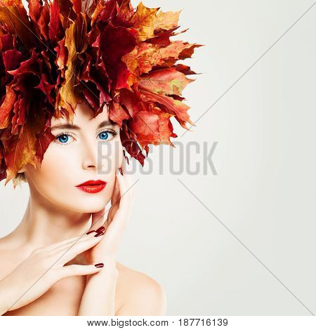 Autumn Lady. Beautiful Woman with Healthy Skin touching her Hand her Face. Makeup Manicure and Fall Leaves Wreath