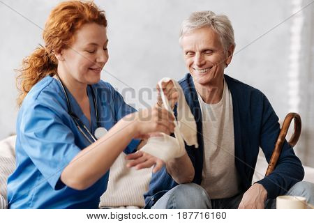 Protecting the joint. Distinguished positive medical worker treating her elderly patient whom she visiting at home by applying special medical bandage