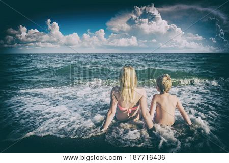 Mother with son sitting on sandy beach in a water and enjoy the seascape. Instagram stylisation.
