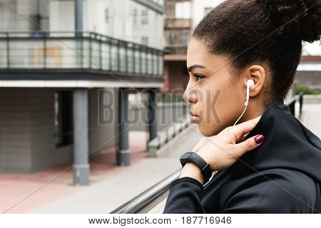 Sporty woman with hooded jacket standing in urban environment, looking away
