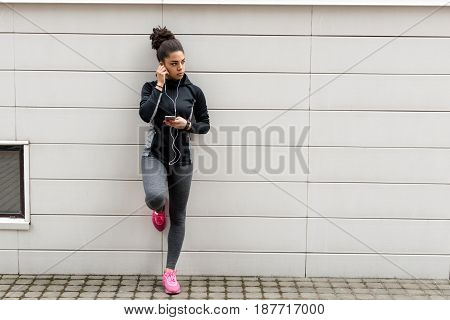 Young female jogger with earphones and smartphone listening to music