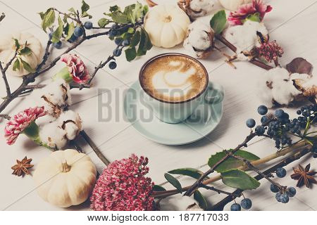 Cappuccino and flowers composition. Blue coffee cup with creamy foam, fresh and dried flowers circle at white wood background.
