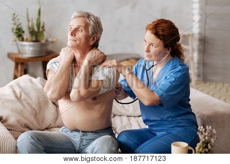 Hold your shirt. Prominent qualified local therapist employing professional equipment for examining patients lungs and figuring out the right diagnosis