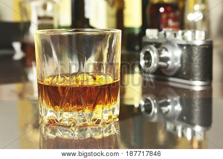 Glass of brandy or cognac and retro camera on the mirror wooden table.