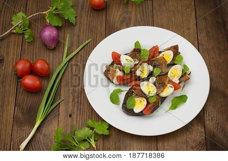 Baked Eggplant With Bacon, Garlic And Quail Eggs. Wooden Background. Top View. Close-up