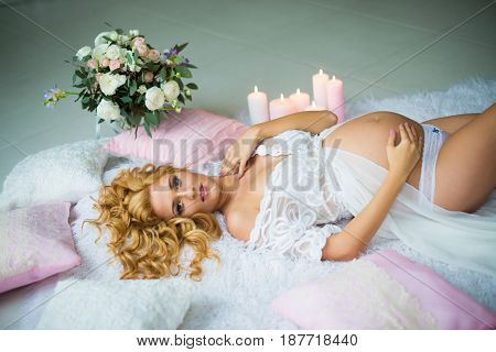 A stunningly beautiful red-haired pregnant girl with fresh flowers. A gentle photo of a pregnant woman. View from above