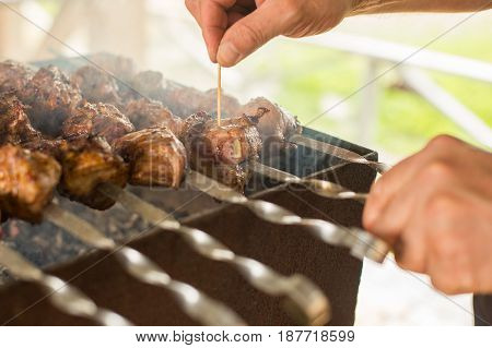The cook prepares a shish kebab on the grill. BBQ party . Close-up.