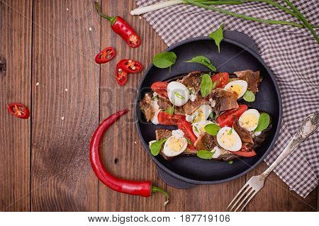 Baked Eggplant With Bacon, Garlic And Quail Eggs On Pan. Wooden Background. Top View. Close-up