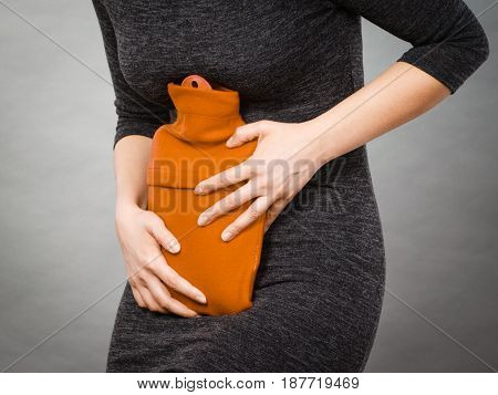 Unrecognizable woman having strong stomach ache. Female suffer on belly pain holding hot red water bottle on abdomen. Health care remedy for pains concept