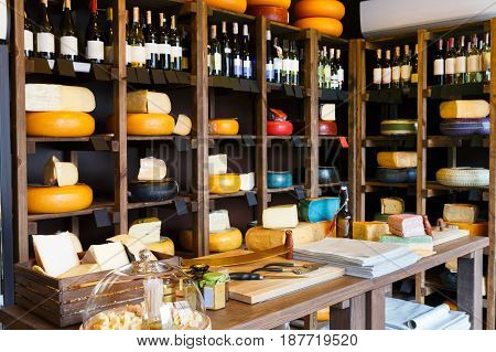 Cheese shop interior, showcase with shelves. Assortment of cheese wheels in store