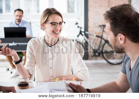 Cheerful manager is sitting near table and looking at colleague with bright smile. They having conversation