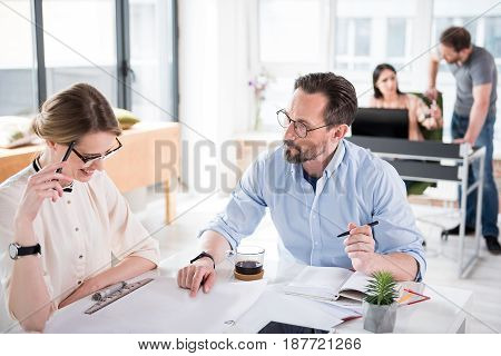 Concentrated manager is helping his female coworker with drafts. She smiling looking down at papers. They sitting near table in office