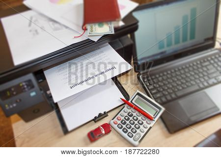 Homeowner and car Insurance form with Laptop Printer pen notebook calculator on the table. Insurance concept