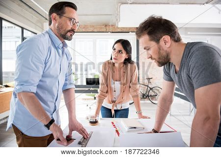 Concentrated male manager is holding ruler and pencil. He looking at colleague with determination. Female coworker attentively glancing aside