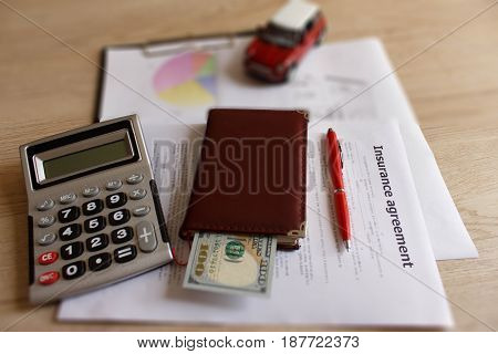 Car and Homeowner Insurance form with pen notebook dollars calculator on the table. Insurance concept