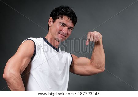 The strong guy is flexing his bicep.
