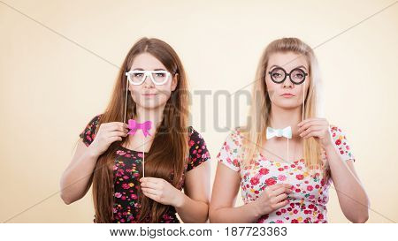 Two Serious Women Holding Carnival Accessoies On Stick