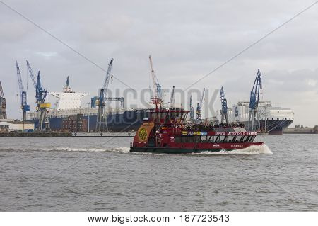 Hamburg Germany - October 29 2016. Boat with tourists goes on Elbe river in Hamburg with cargo traffic in background. It is Germany's largest port and second largest in Europe