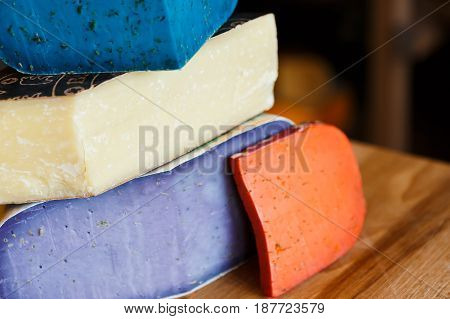 Cheese closeup. Gouda pesto lavender, blue, violet and red at cheese grocery background