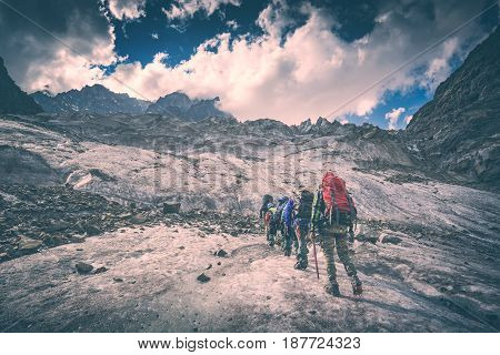 Group of hikers with backpacks climb the glacier to the peak of mountain. Caucasian mountains Georgia Svaneti region. Instagram stylisation.