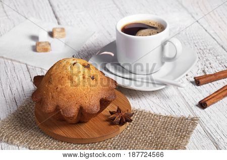 Cupcake with raisins and cup of hot coffee for breakfast on white wooden table